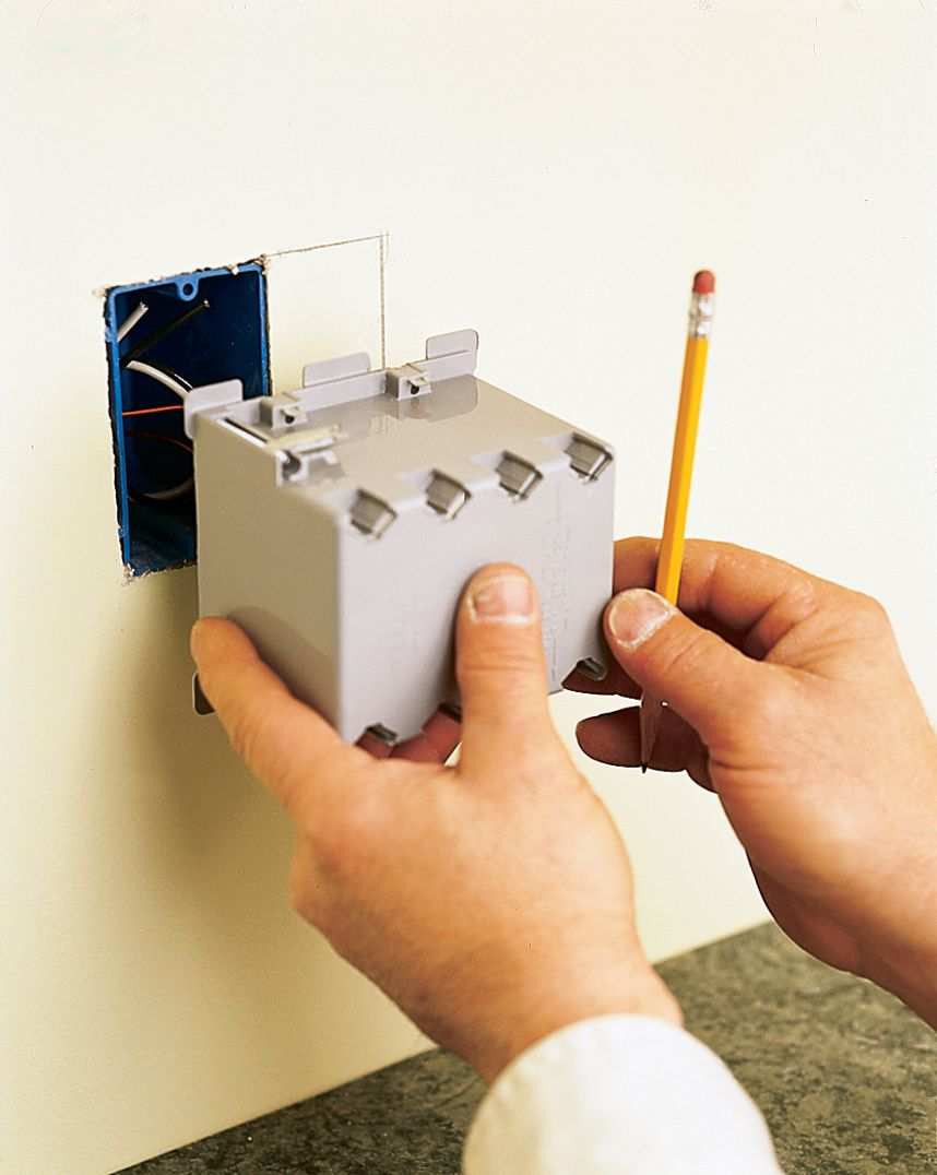 Man Traces Outline Of New Electrical Box For Under Cabinet Lighting Installation