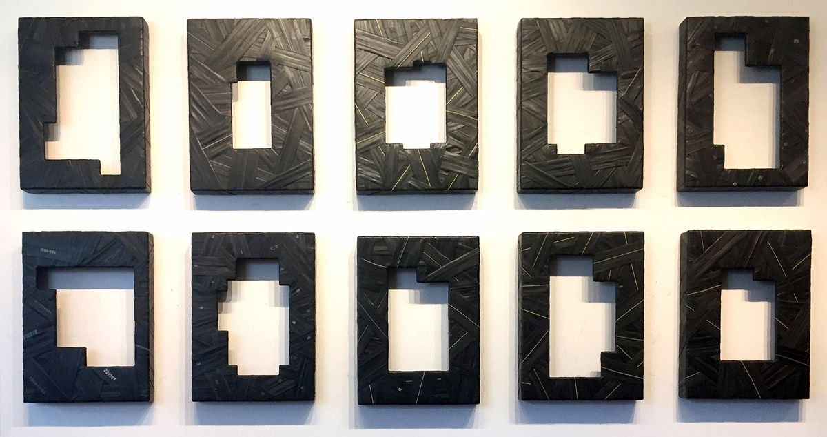 An art piece on a white wall with installation meant to represent homes in black.