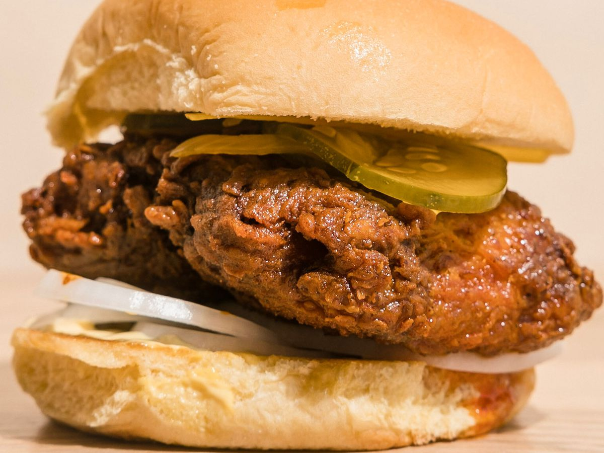 A fried catfish sandwich with onions and pickles.O