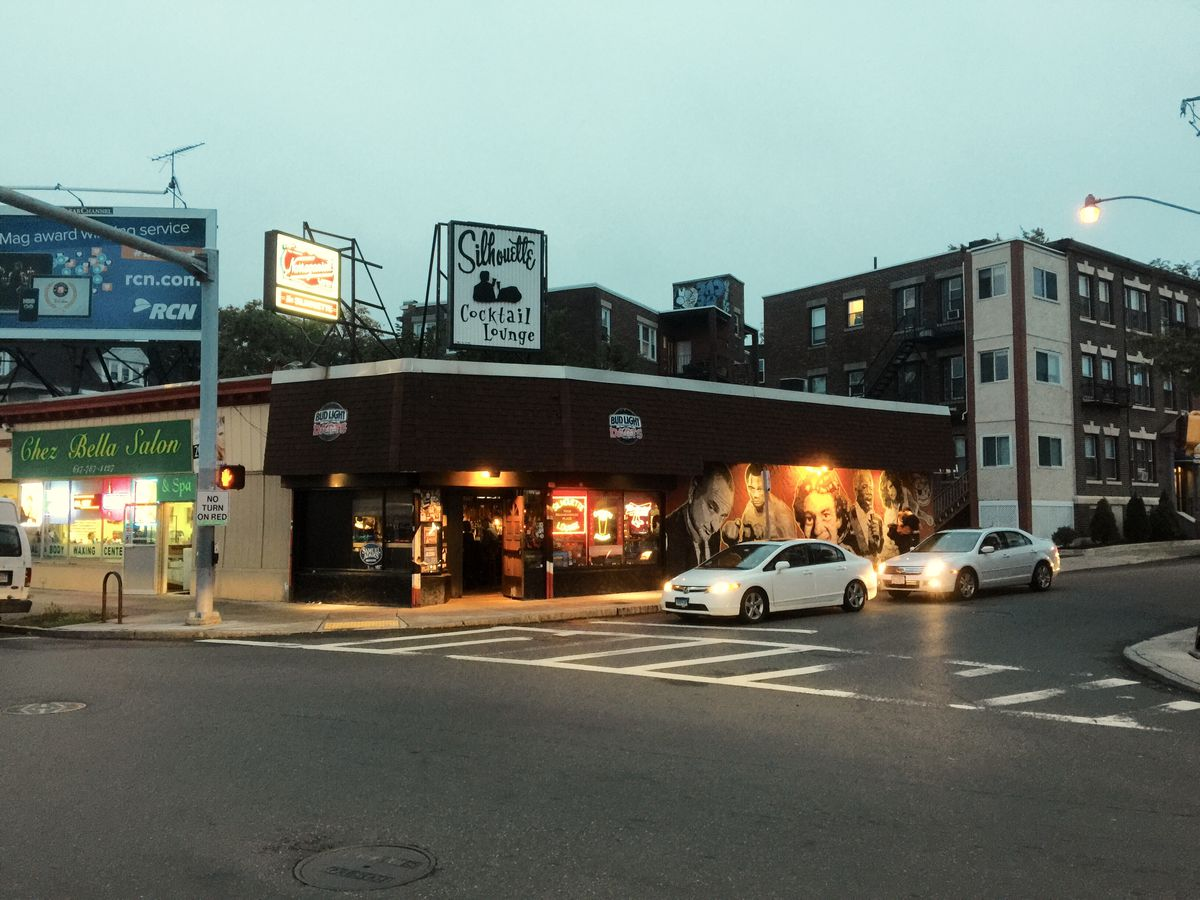 The exterior of a dive bar on the corner of a city street at dusk. Signage reads Silhouette in black cursive, and a colorful mural is painted over one side of the bar's dark exterior.