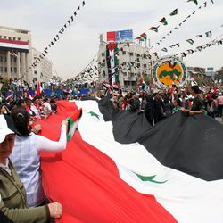 Pro-Syrian government demonstrators carry a giant national flag at a rally at Sabe Bahrat Square to commemorate the 65th anniversary of the foundation of the Ruling Baath Arab Socialist Party in Damascus, Syria, Saturday, April 7, 2012. Syrian President Bashar Assad has accepted a cease-fire deadline brokered by international envoy Kofi Annan, which calls for his forces to pull out of towns and cities by Tuesday and for both government and rebels to lay down their arms by 6 a.m. local time Thursday.(AP Photo Bassem Tellawi)