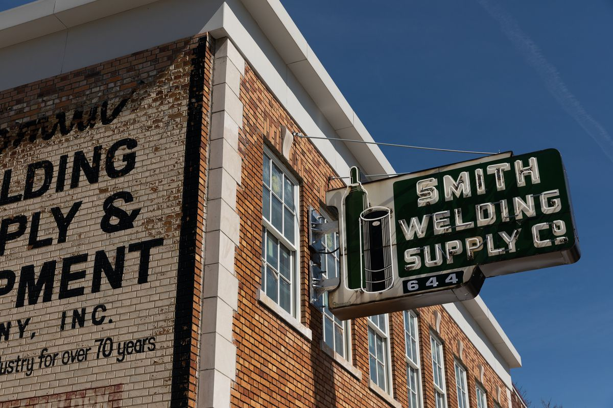 A neon green and white sign for Smith Welding Supply Co. has air canisters on it.