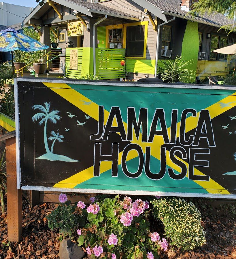 The exterior or the restaurant is seen with a large hand painted sign that reads Jamaica House