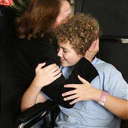 Caleb Ceran gets a hug at University Hospital. Police say an intoxicated driver ran a red light, slamming into the Cerans' vehicle and killing Caleb's mother and two of his siblings.