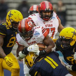 Utah Utes running back Zack Moss (2) is smothered in the line by West Virginia Mountaineers linebacker David Long Jr. (11) and defensive lineman Lamonte McDougle (49) at the Zaxby's Heart of Dallas Bowl between the Utah Utes and the West Virginia Mountaineers in Dallas Texas on Tuesday, Dec. 26, 2017.