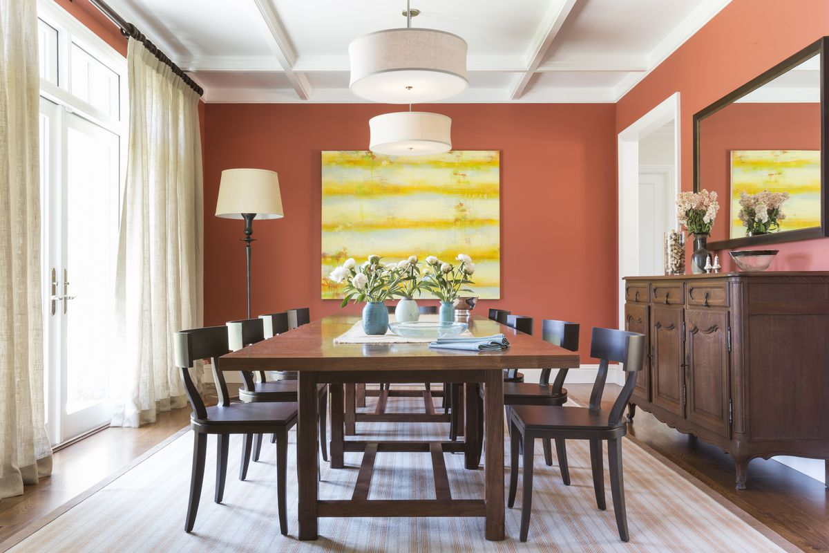 A dining room with orange-red walls.