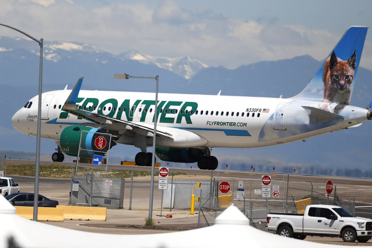 A Frontier Airlines jet heads down a runway for take off from Denver International Airport.