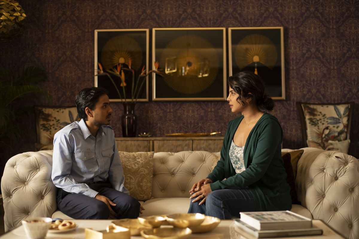 A young man and a woman sit on a couch, talking.
