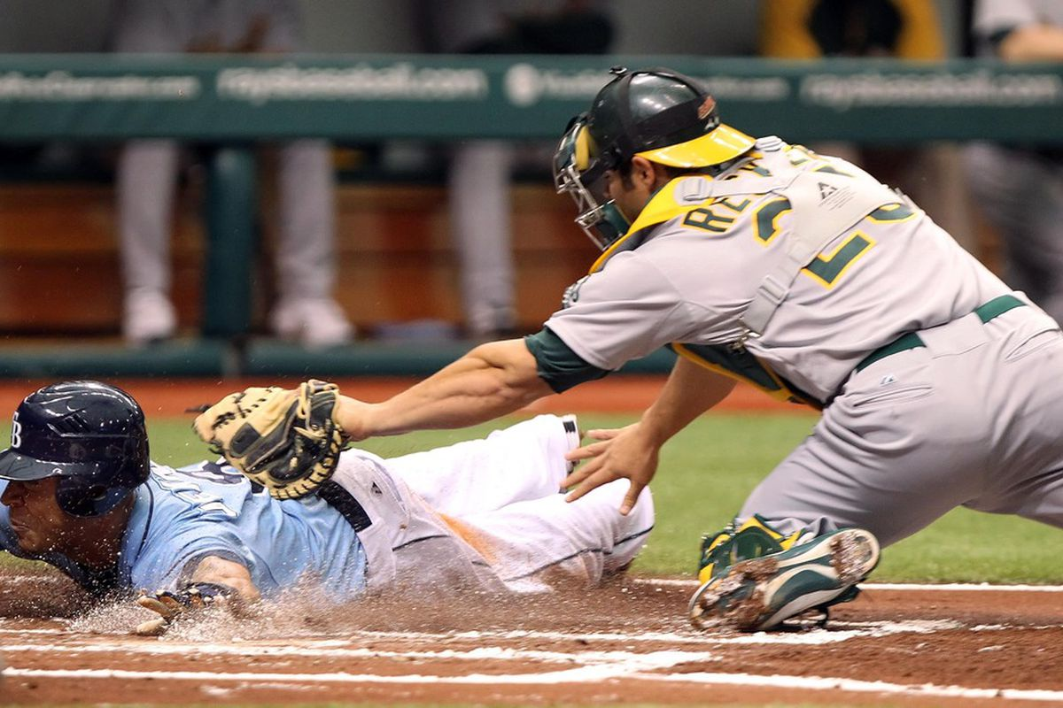 May 5, 2012; St. Petersburg, FL, USA; Tampa Bay Rays left fielder Desmond Jennings (8) slides past Oakland Athletics catcher Anthony Recker (26) in the first inning at Tropicana Field. Mandatory Credit: Kim Klement-US PRESSWIRE