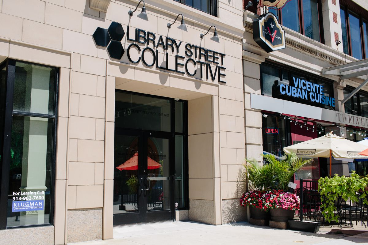 """Outside the front entrance to a brick white stone building. Above the entrance says """"Library Street Collective."""""""