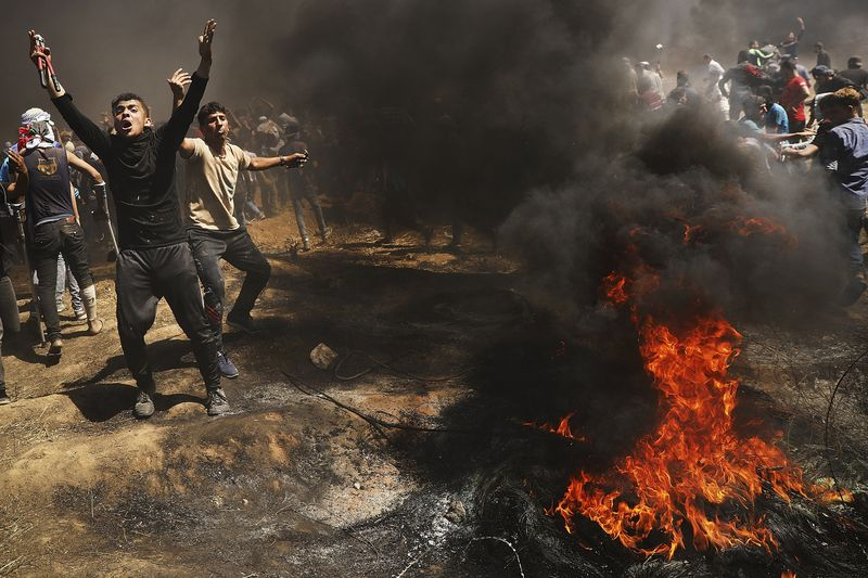 Palestinians protest at the border fence with Israel.