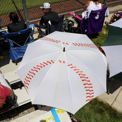 A fan takes cover from the sun under a baseball umbrella as Lone Peak and Riverton compete in a high school baseball game in Highland on Tuesday, June 2, 2020.