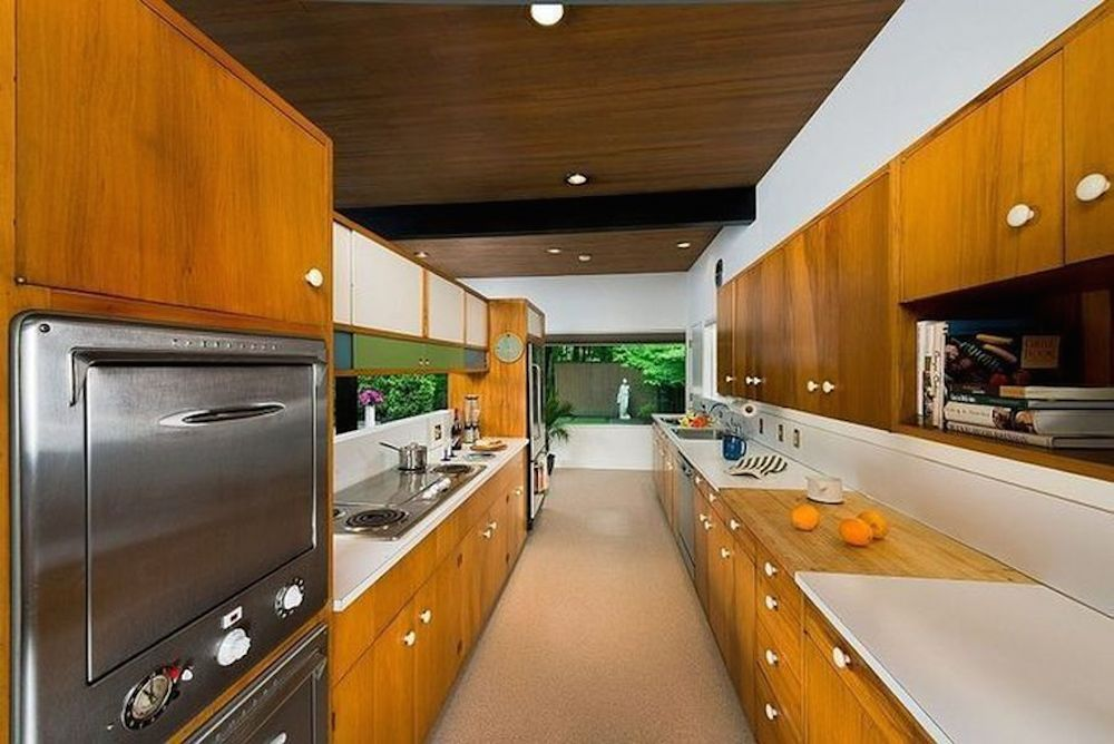 A midcentury kitchen with wood cabinetry and ceiling. The floor is linoleum and the appliances are metallic silver.