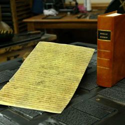 A photograph copy of the original Printers Manuscript for the first printing of the Book of Mormon sits next to a leather bound copy of the first Book of Mormon.