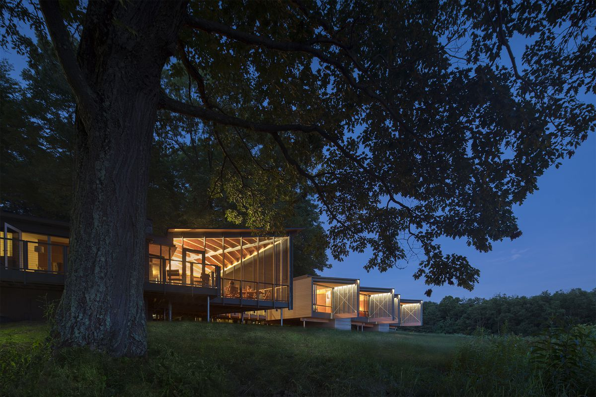 Night shot of cabin-like dwelling on stilts with a screened-in main room and four abodes extending from it.