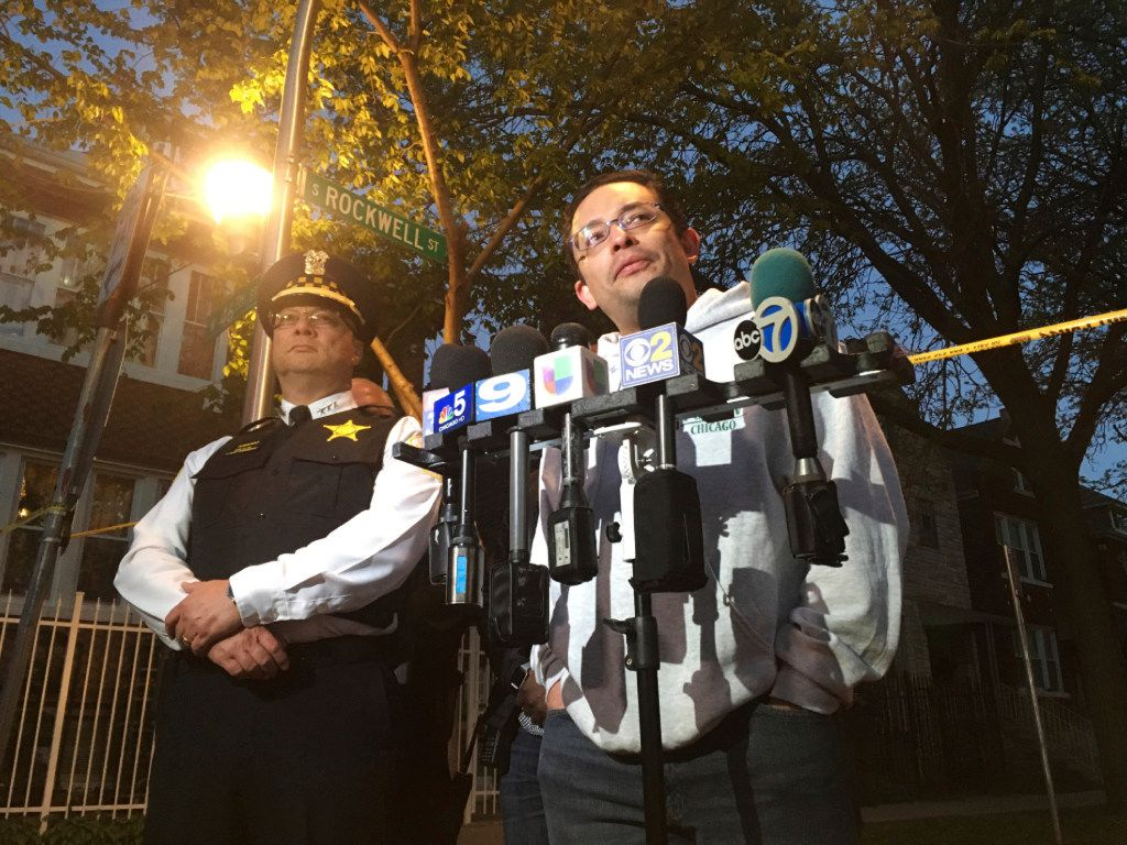 Deputy Police Supt. Kevin Navarro (left) and Ald. Raymond Lopez speak at the scene where suspected gang members opened fire on a group attending a memorial for a man killed earlier Sunday.