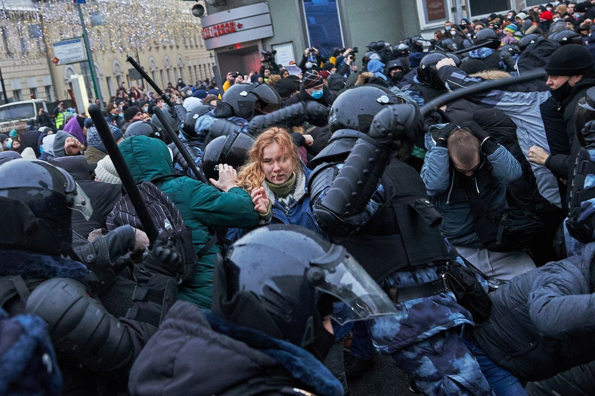 A photo packed with people — tens of black armored police officers batter protesters with their batons; one man tries to escape their blows, ducking low with his hands over his head; a woman with braided red hair stands in the middle of the officers, trapped. In the background, a mass of protesters in winter coats looms.