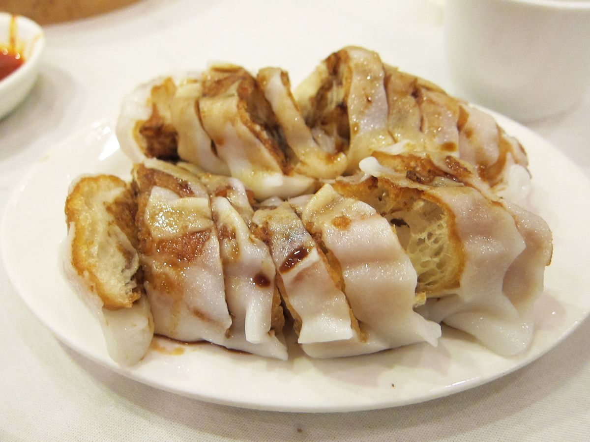 A white plate of sliced rice rolls with yellower cruller peeping through.