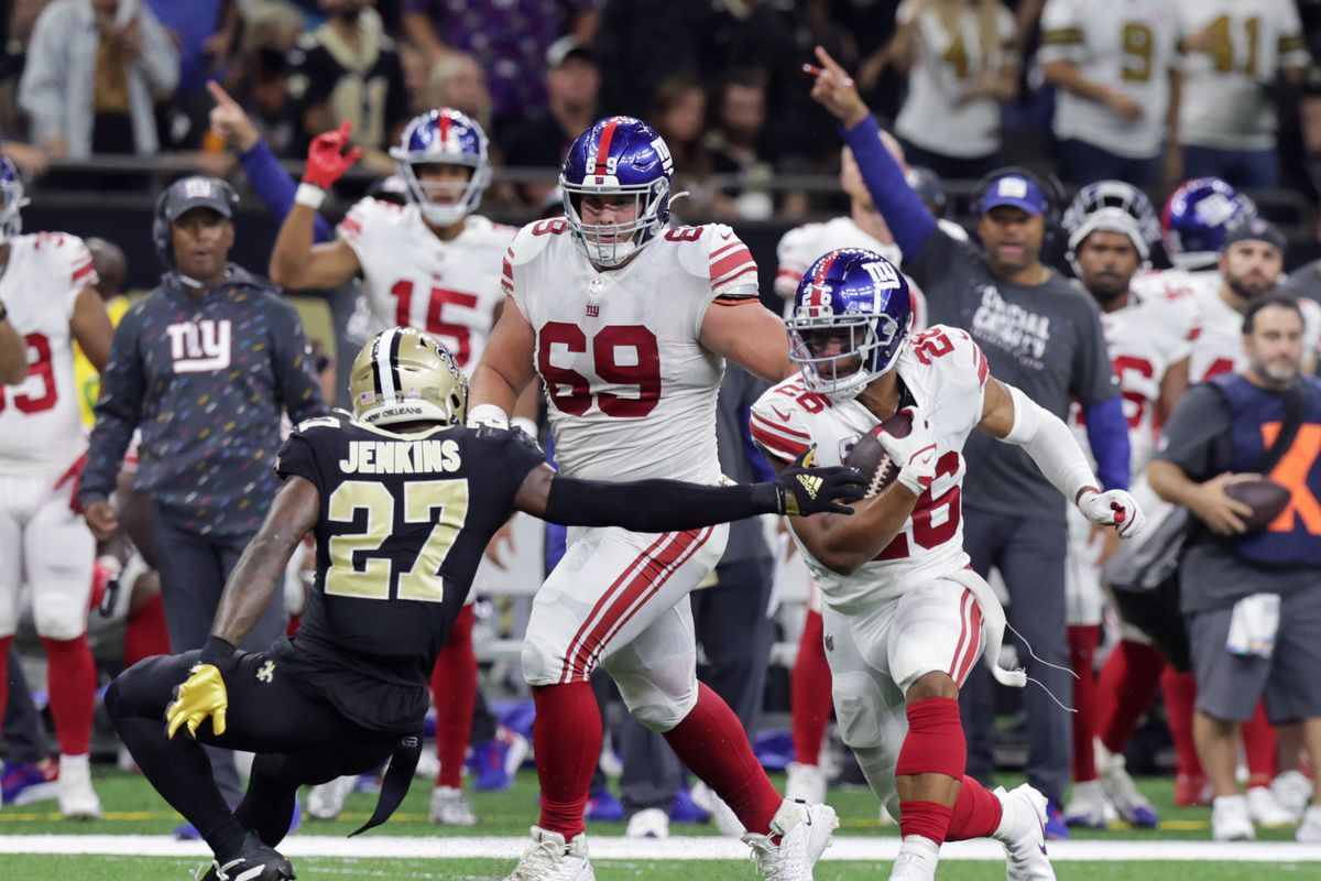 New York Giants running back Saquon Barkley (26) runs around New Orleans Saints strong safety Malcolm Jenkins (27) during the second half at Caesars Superdome.
