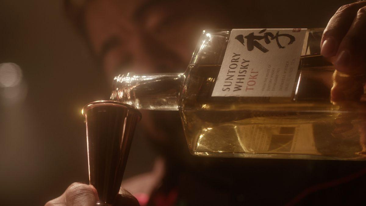 A bartender pours a shot of Suntory Whisky's Toki spirit into a bronze measuring jigger.