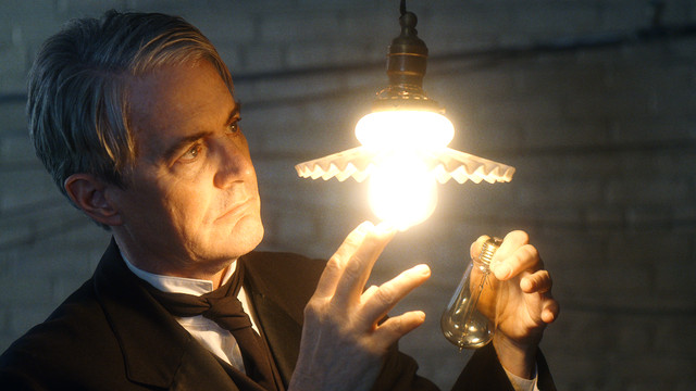 a man inspects a lightbulb