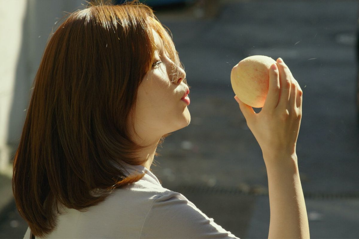 Jessica holds a peach in a still from Oscar-winning film Parasite