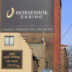 This Thursday, March 22, 2012 photo shows pedestrians walking past a sign introducing the Horeshoe Casino and for gambling help in Cleveland. Casino gambling with its glitz, new jobs and attraction for troubled gamblers is coming to Cleveland, one of America's poorest cities, and experts agree the convenience will increase the number chronic gamblers willing to lie, cheat or steal to get a poker fix.