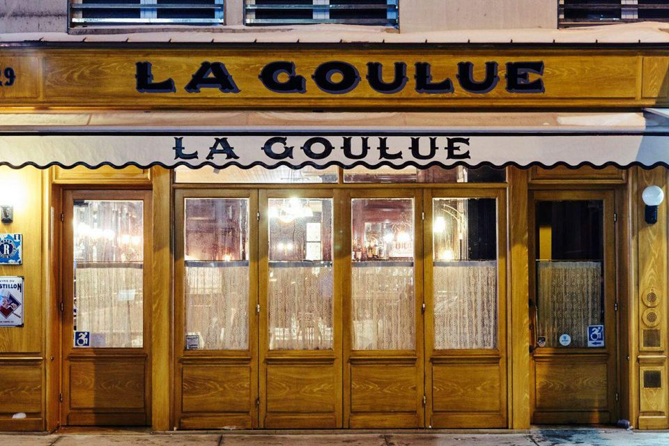 The exterior of a restaurant with brownish-yellow wood with the words la golue written in black