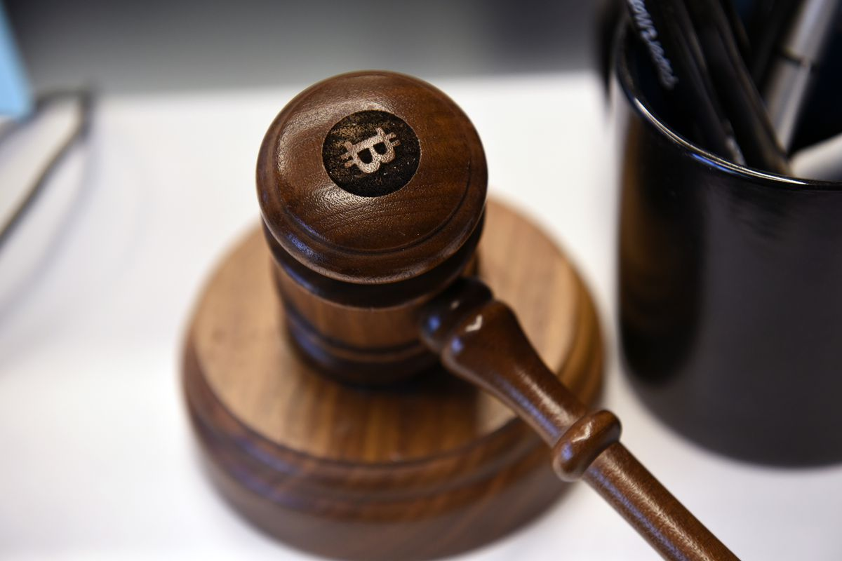 A gavel resting beside a pen cup on a desk sports a bitcoin logo.
