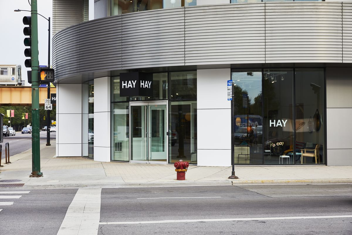 A corner storefront in a low-rise building with floor-to-ceiling glass windows and a metal panels.