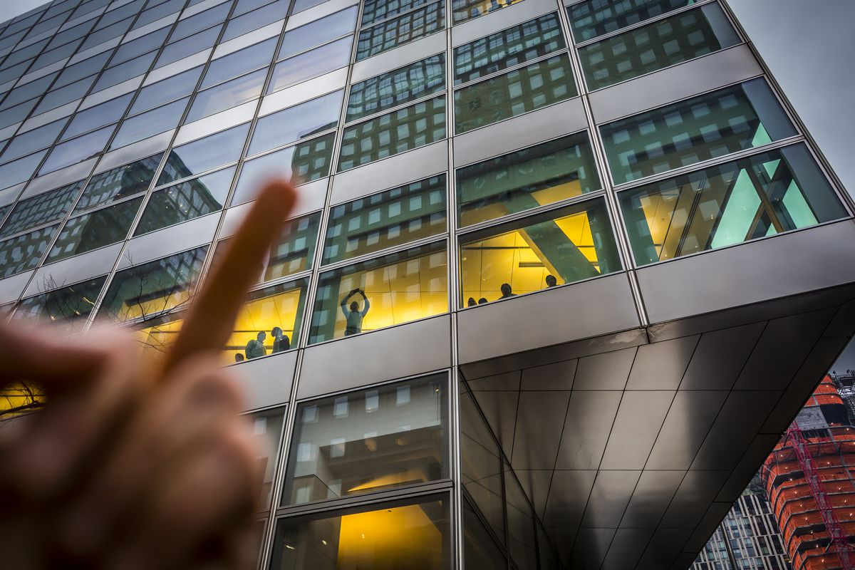 A hand making a raised middle finger gesture in front of the Goldman Sachs building in New York City.