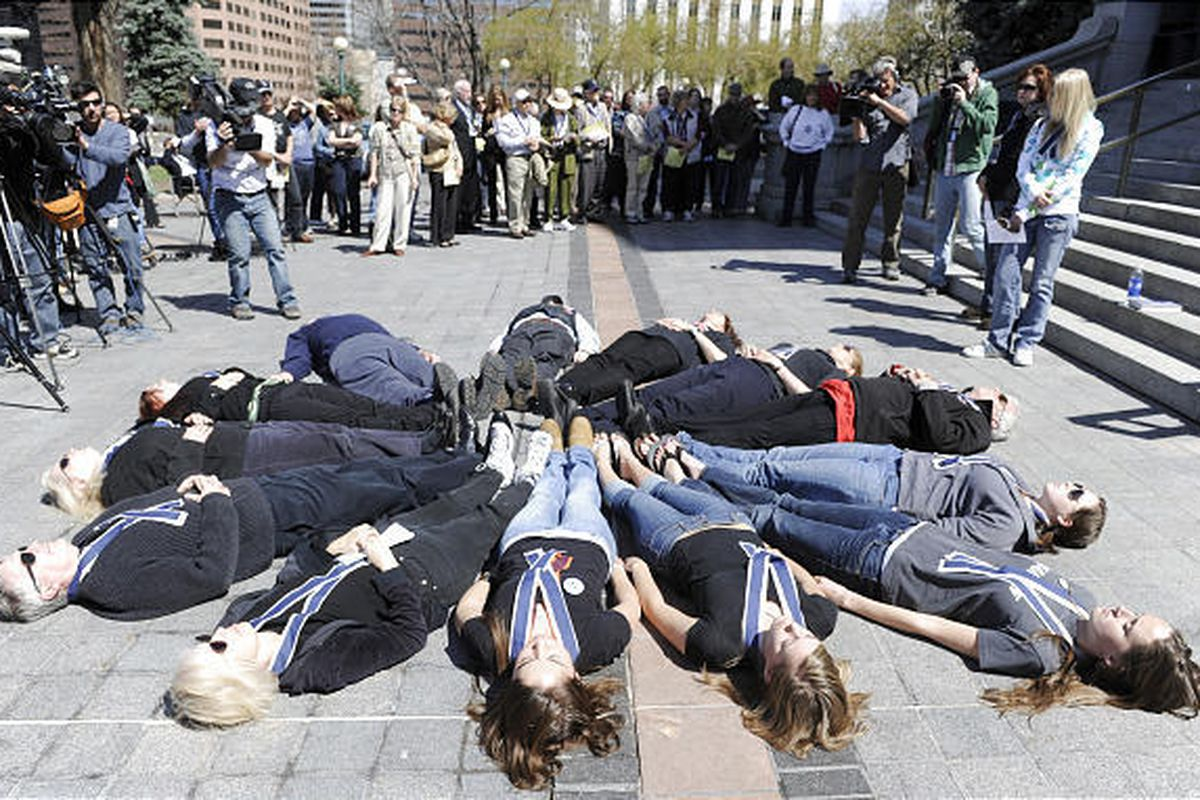 Thirteen people lay down to symbolize those killed in the Columbine school shooting at a Columbine Remembrance and Rededication on the 10th anniversary of the Columbine attack, at the Capitol in Denver, on Monday.