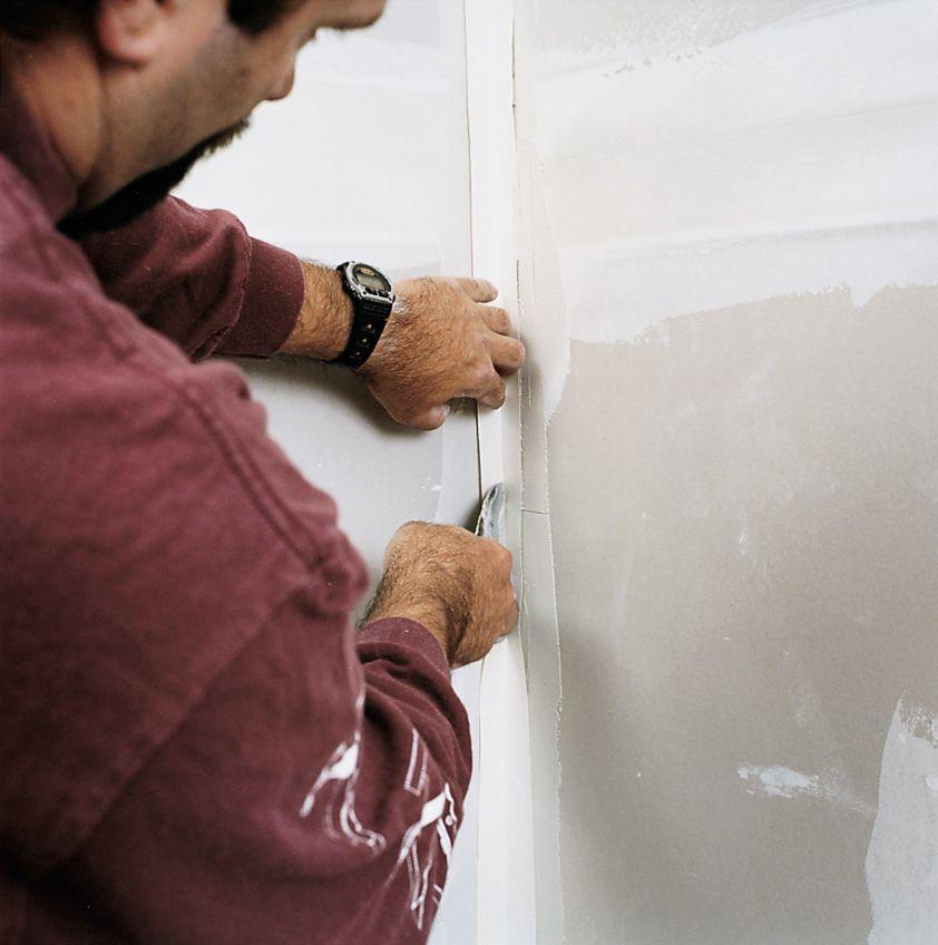 Ленты Man внутри углов стены с лентой гипсокартона