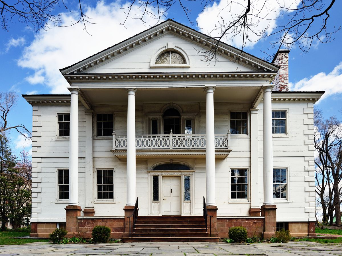 The exterior of the Morris-Jumel Mansion in New York City. The facade is white with columns and a wraparound porch and staircase.