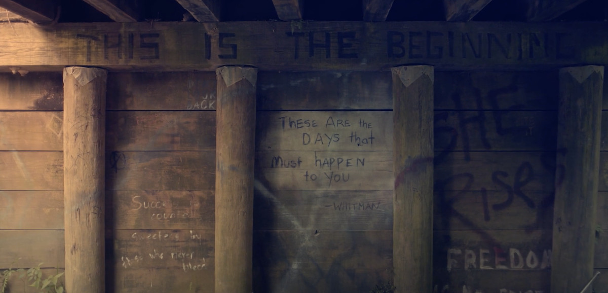 a smoking area beneath a wooden bridge, with quotes written on the walls, in Looking for Alaska