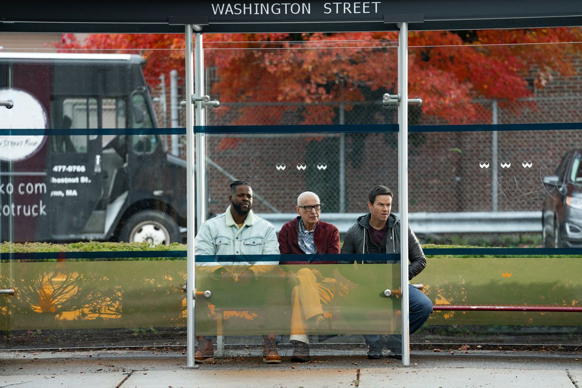 The three men sitting at a bus stop.