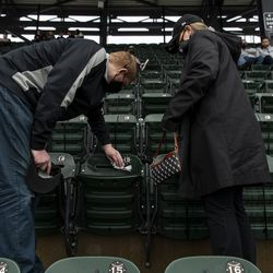 Chicago White Sox fans David Urbauer, left, and Lauren Simon wipe down their chairs of rain water, at Guaranteed Rate Field during the White Sox home opener against the Kansas City Royals, Thursday, April 8, 2021.