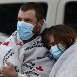 Andrew and Jessica Nicoll watch South Salt Lake firefighters clean up after an early morning fire at their apartment complex in South Salt Lake on Thursday, April 16, 2020. The Nicolls'apartment suffered minor damage.