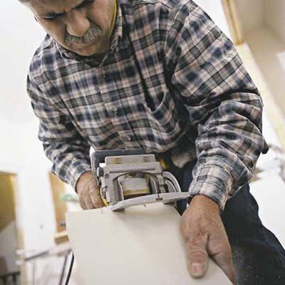 Man Cuts Biscuit Slots On Baseboard With Biscuit Joiner