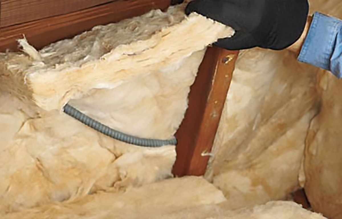 Man Halves Batt's Thickness And Slides Wire In Front Of Other Half For Wall Insulation