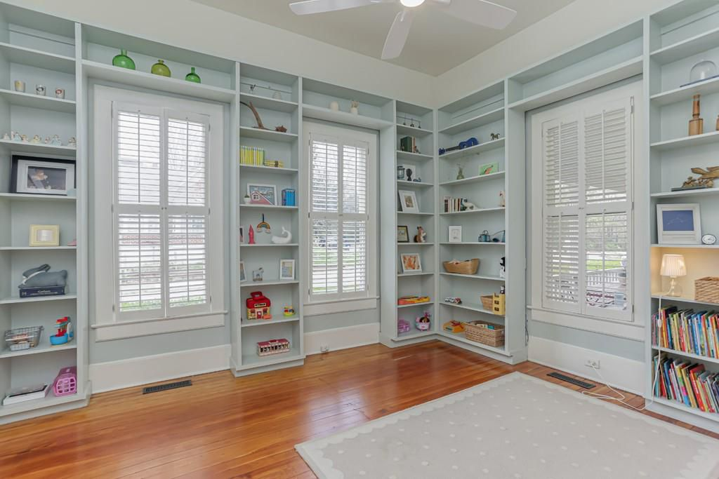 A room with a huge built-in books cases painted light blue.