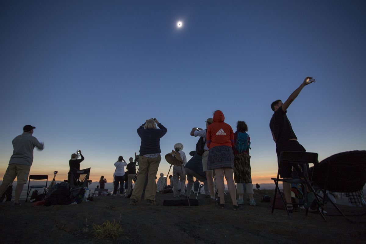 A crowd in Idaho watches the sky darken as the solar eclipse approaches totality.