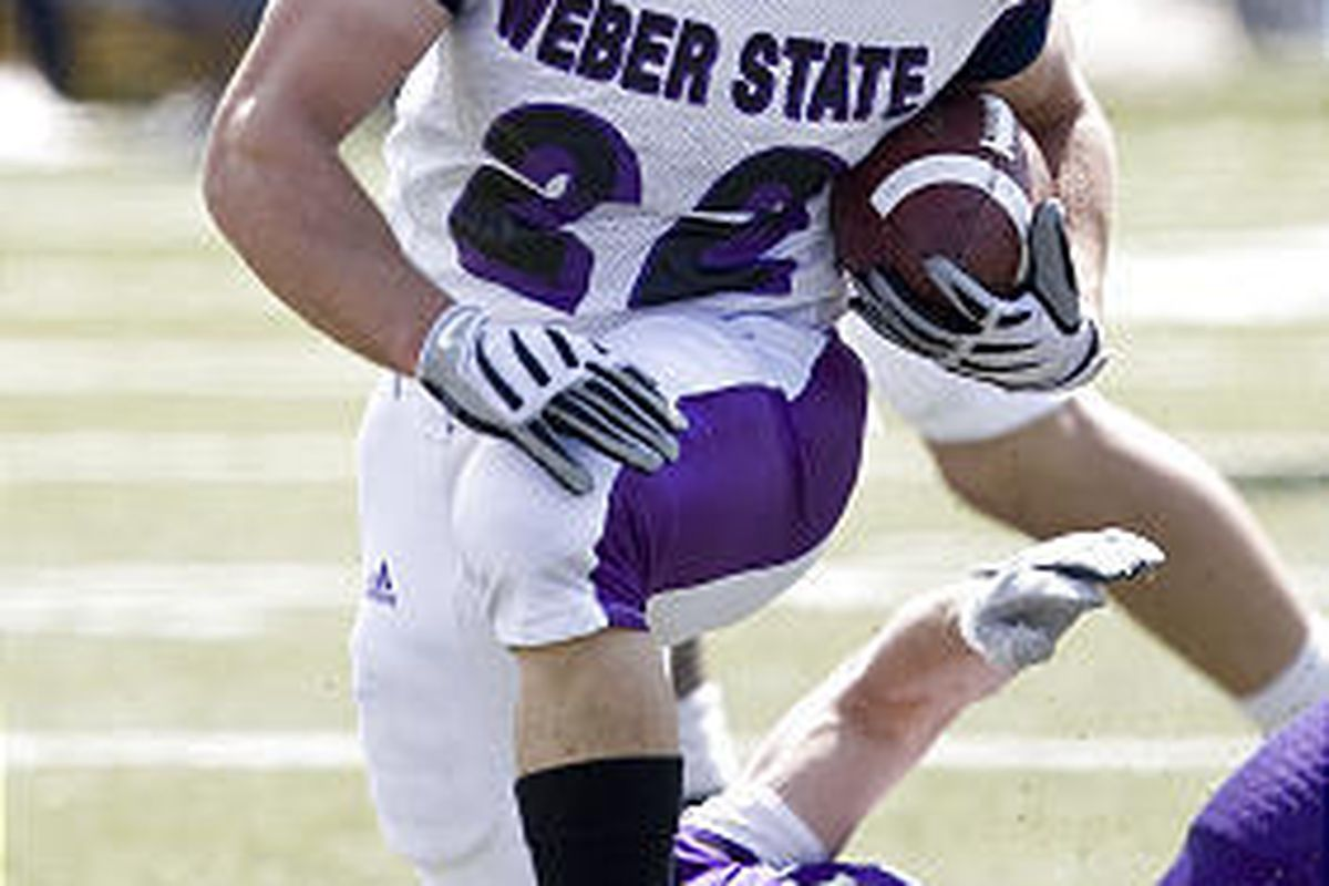 Weber State running back C.J. Tuckett carries the ball as Wildcat football players participate in the annual Purple and White spring game in Ogden in 2009.