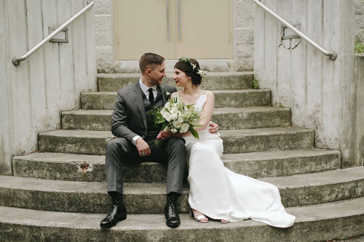 A bride and groom sitting on steps
