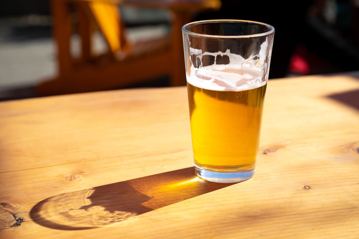 A close up on a pint glass of amber pale ale beer, casting a shadow on a wood table.
