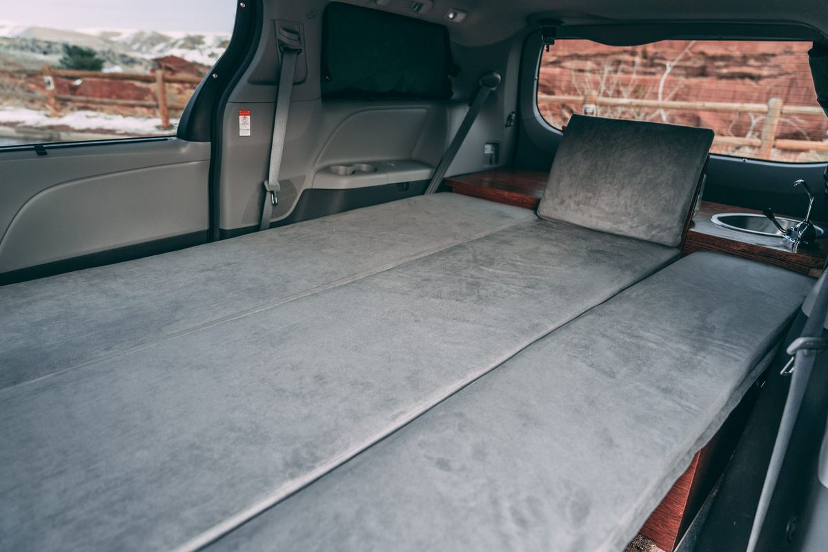The interior of an Oasis Campervan. The seats are expanded into a bed.