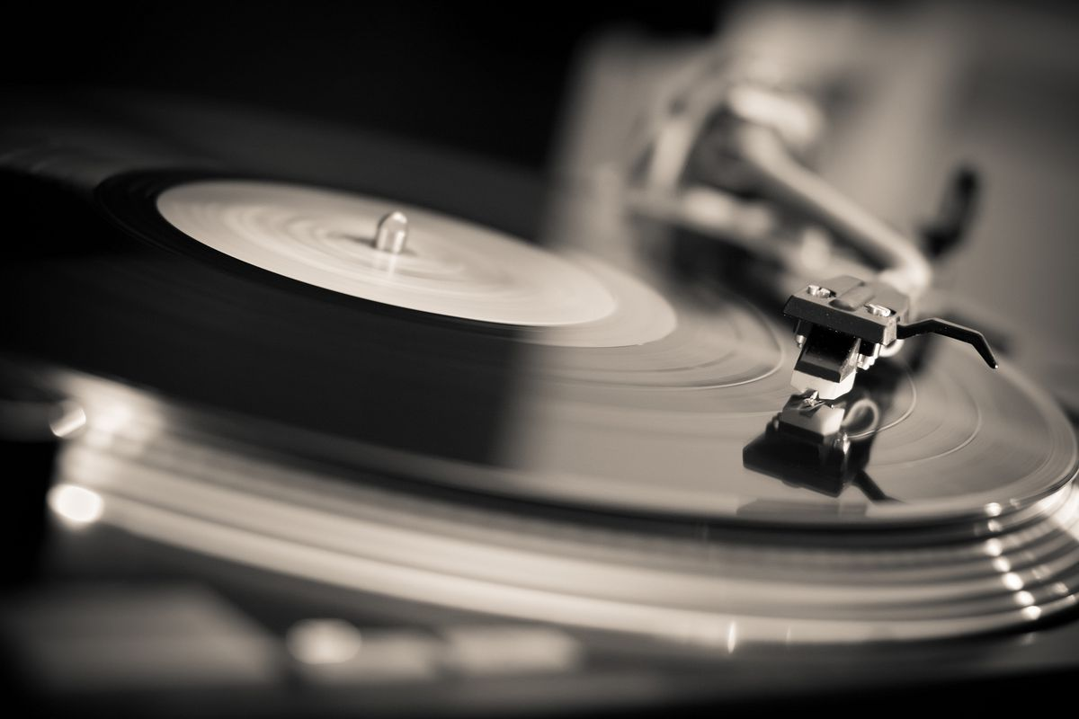 A vinyl record spins on a turntable
