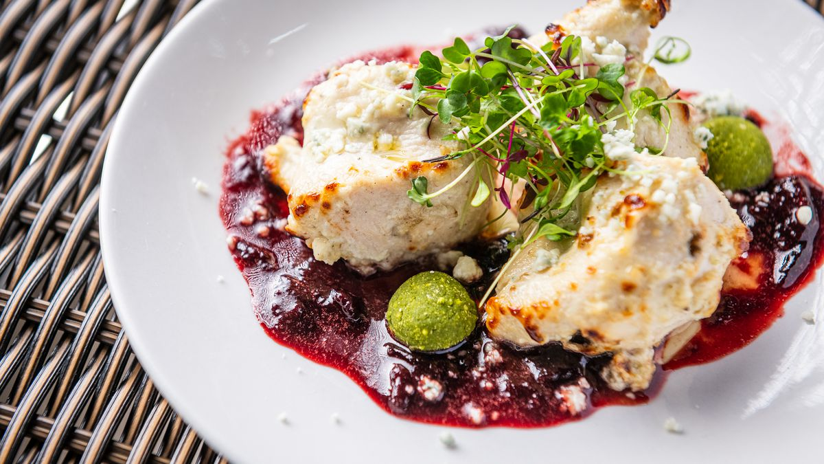 Pieces of chicken from Daru's reshmi kebab are coated in a yogurt and blue cheese marinade while sitting above a deep red sour cherry sauce and chutney spheres.