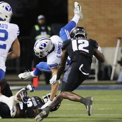 Brigham Young Cougars wide receiver Gunner Romney (18) is upended by Utah State Aggies safety Ajani Carter (12) in Logan on Friday, Oct. 1, 2021.