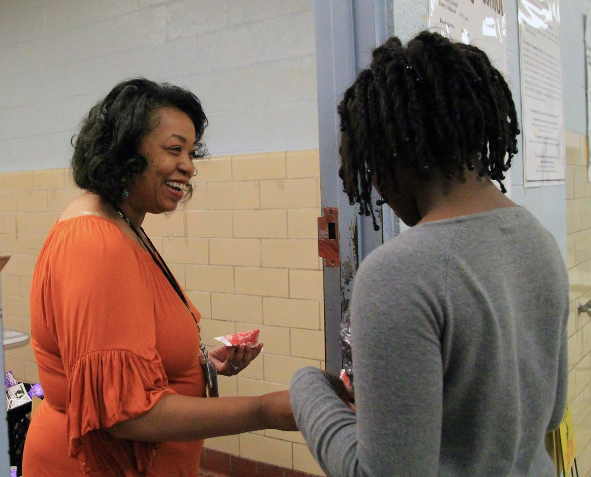 Cheryl Williams hands out lunch to aline of hungry students at Cummings.